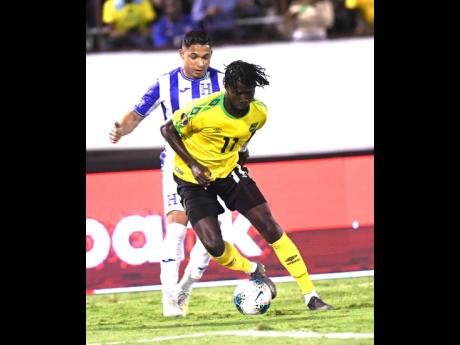 Jamaica's Shamar Nicholson (front) dribbles ahead of Honduran player Emilio Izaguirre in their Group C Concacaf Gold Cup match at the National Stadium on Monday night.