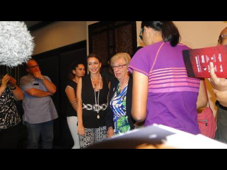 Holocaust survivor Eva Schloss is surrounded by people who are eager for a photo opportunity with her inside The Jamaica Pegasus hotel on April 2. PHOTO BY Paul H. Williams
