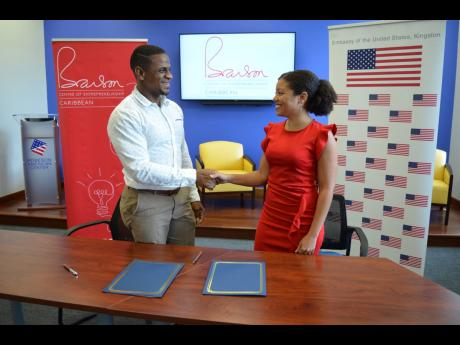 The United States Embassy Kingston's counsellor for public affairs Jeremiah Knight (left), and Branson Centre Caribbean CEO Lisandra Rickards formalise a commitment to complement each other's missions for the development of Jamaica's entrepreneurial ecosystem by hosting specialised fireside chats throughout the year under the theme 'Journeys to Scale' at the Robeson American Center.