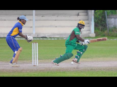 Clarendon's Albert Gopie (right) works a ball to the offside while St Elizabeth wicketkeeper Rahjni Roye looks on during their Jamaica Cricket Association T20 Bashment encounter at Chedwin Park on Saturday,  July, 8.