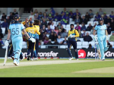 Sri Lanka's Lasith Malinga (centre left without cap) celebrates with teammates after the dismissal of England's Jos Buttler (right) during their ICC World Cup match in Leeds, England, yesterday.