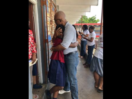 Kirah Malcolm is congratulated by her dad, Howard Malcolm, on hearing news that she had passed for Holy Childhood High.