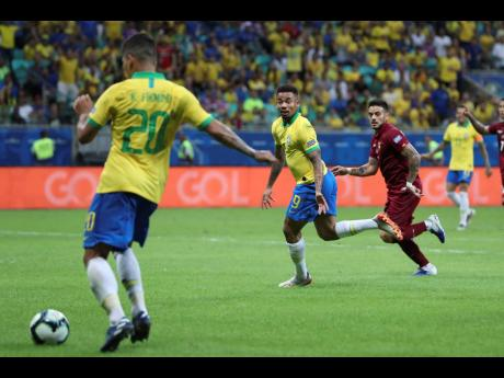 Brazil's Roberto Firmino (left) passes the ball to teammate Gabriel Jesus (centre) to score a goal that was disallowed by the referee during a Copa América Group A match against Venezuela at the Arena Fonte Nova in Salvador, Brazil, on Tuesday.