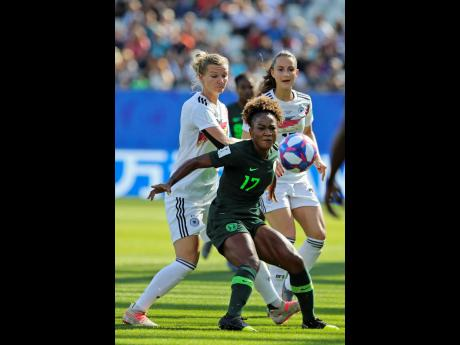 Nigeria's Francisca Ordega (front) vies for the ball with Germany's Alexandra Popp during the Women's World Cup Round of 16 match between Germany and Nigeria at the Stade des Alpes in Grenoble, France, yesterday. Germany won 3-0.