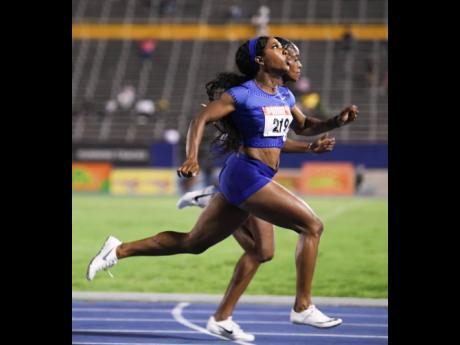 Elaine Thompson (background) edges Shelly-Ann Fraser-Pryce to the line in the women's 100m final at the Supreme Ventures/JAAA National Senior Championships at the National Stadium on Friday night. Both athletes were clocked at 10.73 seconds.