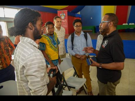 Ian Boxill, founder of GATFFEST (right), speaks with young film-makers and participants following  GATFFEST's Film Pitch competition at The UWI, Mona, on Saturday.