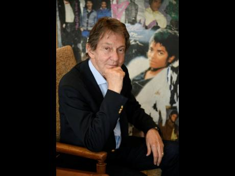 In this Tuesday, June 18, 2019 photo, entertainment and corporate lawyer John Branca, the co-executor of Michael Jackson's estate, poses in his office, at the law firm of Ziffren Brittenham LLP in Los Angeles, next to an artwork presented to him from Sony Music commemorating the sale of 100 million copies of Michael Jackson's album 'Thriller'.  .