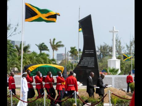 Members of the 1st Battalion Jamaica Regiment carry the coffin bearing the body of Edward Seaga past the monument memorialising his great political arch-rival, Michael Manley, at National Heroes Park yesterday afternoon. Gladstone Taylor/Multimedia Photo Editor
