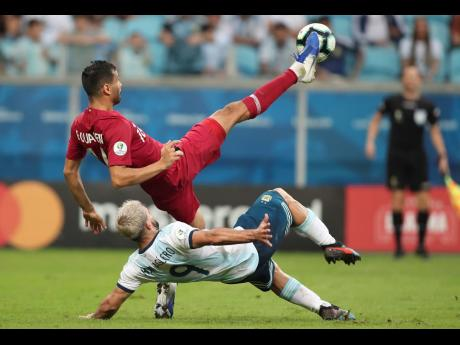 Qatar's Boualem Khoukhi (above) and Argentina's Sergio Aguero fight  for the ball during a Copa America Group B match at the Arena do Gremio in Porto Alegre, Brazil, yesterday.