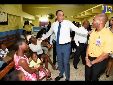 Health Minister, Dr. Christopher Tufton (second right), interacts with Dr. Richard Manning (right) and patients of the Seaview Gardens Health Centre in Kingston  during a ceremony on April 30, when the clinic was formally adopted by Massy Distribution (Jamaica) Limited under the Ministry of Health's Adopt-a-Clinic programme.