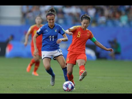 China's Wu Haiyan (right) tussles for the ball with Italy's Barbara Bonansea during the Women's World Cup round of 16 match between Italy and China at Stade de la Mosson in Montpellier, France, yesterday. Italy won 2-0.