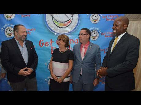 Minister without portfolio in the Ministry of Economic Growth and Job Creation, Daryl Vaz (second right), shares a light moment with (from left) Kurt Kleess, vice-president of global sales at Enterprise Electronics Corporation; Galina Sotirova, World Bank country manager; and Dr Wayne Henry, director general of the Planning Institute of Jamaica, and at the signing ceremony for the instalation of a new weather radar system yesterday.