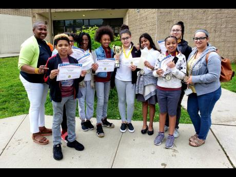 Students of Johnnie L. Cochran Junior Academy in East Orange, New Jersey, who won the inaugural Schools' Challenge Quiz Bowl USA  competition, with Narda Morant (left), event founder and director, and Adalgisa Sosa (right), teacher and quiz coach at the school.