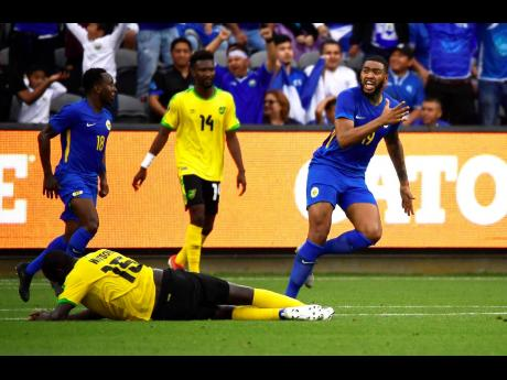 Curaçao forward Jafar Arias (right) celebrates a goal by Jurien Gaari as Jamaica midfielder Je-Vaughn Watson lies on the ground during the second half of a Concacaf Gold Cup match on Tuesday in Los Angeles. The game ended 1-1.