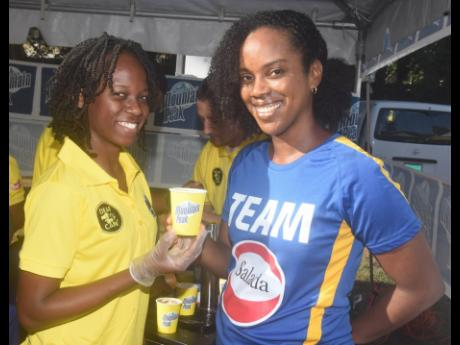 It's all smiles asDeaf Can! Coffee Barista Wadia Barnes (left) presents Tamii Brown, Salada Foods Jamaica commercial and corporate affairs manager, with a sample of the special Jamaica Mountain Peak Nitro Cold Coffee brew made for the Father's Day edition of the Everyone's a Winner the Best Dressed Chicken 5K, 10K & 3K road race to on Sunday, June 16, at Hope Gardens. The Jamaica Association for the Deaf was one of the charity partners for the event.