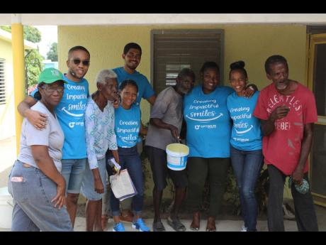 Team members from Optimum Trading and residents at the Golden Age Home pause working for some lens time.