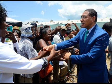 Prime Minister Andrew Holness (right) greets residents of St Thomas who turned out to witness the groundbreaking of the Morant Bay Urban Centre at the old Goodyear Factory on Wednesday.