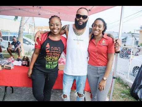 Reshima Kelly, junior brand manager for Red Stripe, shares a moment with Chicken and Beer (centre) and Nicole Hall, marketing coordinator at CB Foods, at the community launch of their summer promotion, 'Chicken and Beer', in Nannyville.