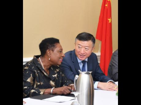 Sport minister Olivia Grange (left) shares a light moment with the Ambassador of the People's Republic of China to Jamaica, Tian Qi. They were at the official send-off, on Tuesday, for the second batch of 138 Jamaican athletes and coaches who will receive specialised training in China under a sports cooperation agreement between both countries.