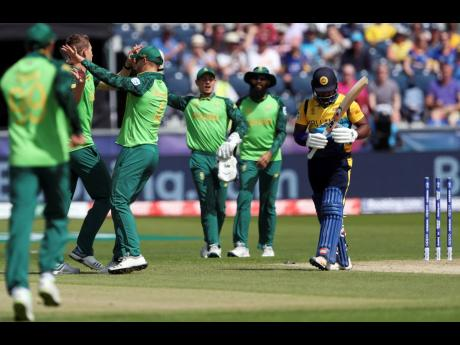 South Africa bowler Dwaine Pretorius (far left) celebrates with teammates after bowling Sri Lanka batsman Kusal Perera (far right) for 30 runs during their Cricket World Cup match at the Riverside Ground in Chester-le-Street, England, yesterday.
