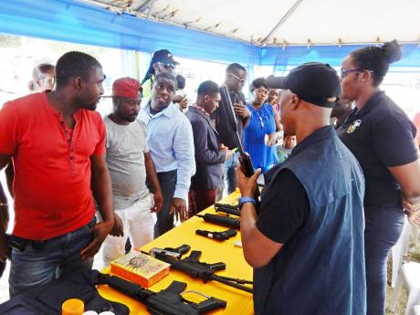 Persons gather at the Customs Agency booth that has on display some items that are banned.