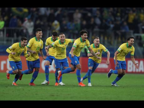 Brazil's players celebrate winning at the end of the Copa Amêrica quarter-final match against Paraguay at the Arena do Gêmio in Porto Alegre on Thursday.