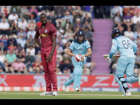 West Indies' Carlos Brathwaite (left) reacts after being hit for four by England's Joe Root (right) during their Cricket World Cup match at the Hampshire Bowl in Southampton, England, on June 14.