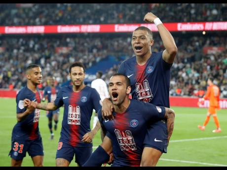 PSG's Kylian Mbappe, top, celebrates with teammate Dani Alves after scoring the third goal during the French League One football match between Paris-Saint-Germain and Monaco at the Parc des Princes stadium in Paris on April 21.