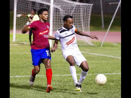 Dunbeholden's Adrian Williams and Cavalier's Nicholas Hamilton (right) duel for the ball in their Red Stripe Premier League match at the Stadium East Field on Sunday, December 16, 2018.