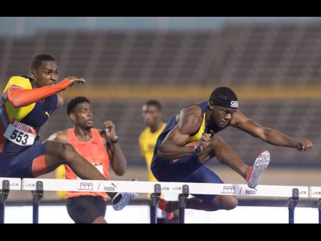 Orlando Bennett (right) clears a hurdle ahead of Olympian Hansle Parchment (left) while competing in the men's 110m hurdles final at the JAAA/Supreme Ventures National Senior Athletics Championships at the National Stadium on Sunday. Bennett, with a time of 13.27 seconds, placed second to Ronald Levy (not pictured).
