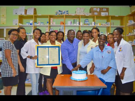 Staff of the Drug Serv Pharmacy at the Greater Portmore Health Centre were presented with the ISO 9001:2015 certification and a well-deserved treat from the chief executive officer, Everton Anderson (centre). Joining in the celebration are Michelle Sturridge (left), manager, National Certification Body of Jamaica, and Audriana Sinclair (second left), quality assurance manager, NHF.