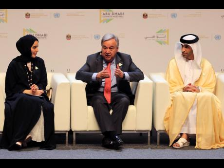 United Nations Secretary General Antonio Guterres (centre) talks to the audience as UAE Youth Minister Shamma Al Mazrim (left) and Thani bin Ahmed Al Zeyoudi, UAE minister of climate change and environment, listen at the opening ceremony of the United Nations Climate Change summit in Abu Dhabi, United Arab Emirates, yesterday.