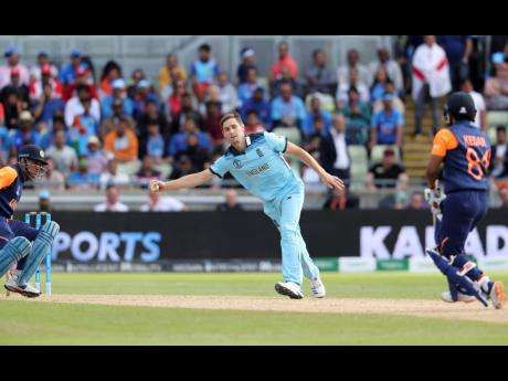 England's Chris Woakes (centre) fields off his own bowling during the ICC World Cup match against India in Birmingham, England, yesterday.