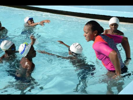 Alia Atkinson teaching children to swim at a clinic held at the University of The West Indies swimming pool on Tuesday, December 19, 2017.