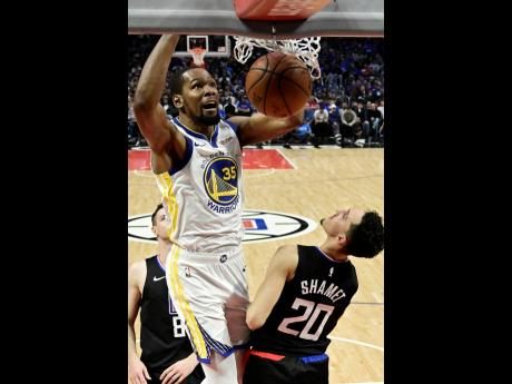 Golden State Warriors forward Kevin Durant (top) dunks as Los Angeles Clippers guard Landry Shamet defends during the second half of Game 4 of a first-round NBA play-off series in Los Angeles, California, on Sunday, April 21.