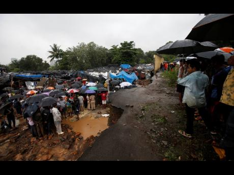 Rescuers and others gather at the spot after heavy rainfall caused a wall to collapse onto shanties, in Mumbai, India, Tuesday, July 2, 2019. More than a dozen people were killed even as forecasters warned of more rains. (AP Photo/Rafiq Maqbool)