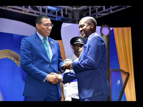Prime Minister Andrew Holness (left) presents Jamaica Teachers' Association Regional Officer Clayton Hall with the Prime Minister's Medal of Appreciation for Service to Education, during the awards ceremony at Jamaica House on June 26.