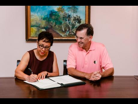 Founder and CEO of Salamander Hotels and Resorts Sheila Johnson and Chairman of Half Moon Guy Steuart III sign the agreement for Salamander to manage the luxury resort in Montego Bay.