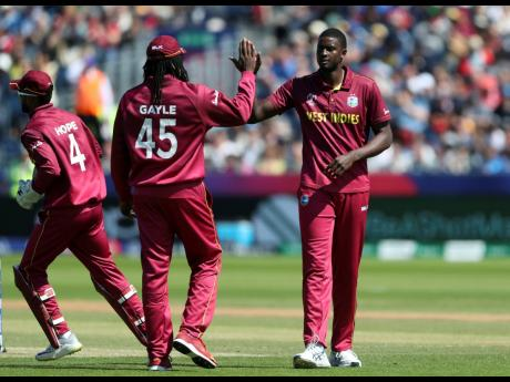 West Indies captain Jason Holder (right) celebrates with teammate Chris Gayle (middle) after dismissing Sri Lanka's captain Dimuth Karunaratne during their Cricket World Cup match at the Riverside Ground in Chester-le-Street, England, on Monday, July 1, 2019.