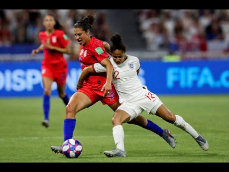England's Demi Stokes (right) and the United States' Carli Lloyd duel for their ball during the Women's World Cup semi-final match at the Stade de Lyon outside Lyon, France, yesterday. The USA won 2-1.