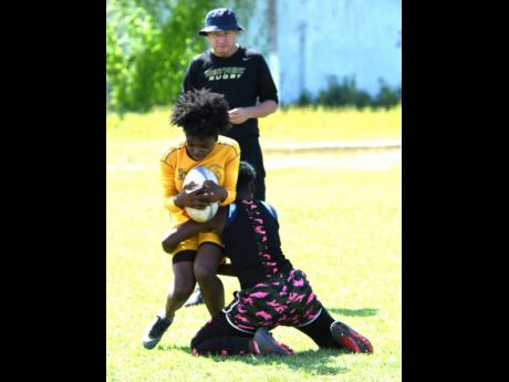 Members of the Jamaica rugby union Lady Crocs team participating in a training session under the watchful eye of coach Stephen Lewis at Emmett Park on Saturday, June 29, 2019.