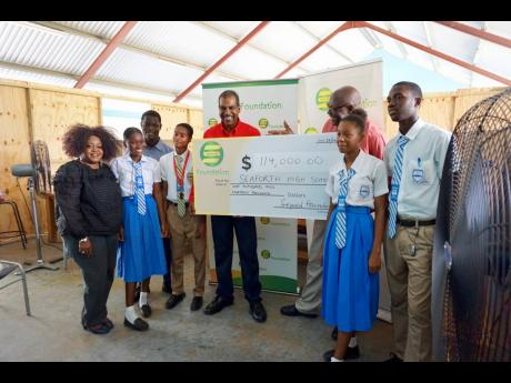 From left: Seaforth High School arts teacher Caroline Miles, Serge Island general manager Dr Gavin Bellamy, and Seaforth High principal Calbert Thomas are joined by members of the school's student body for a cheque handover from Seprod.