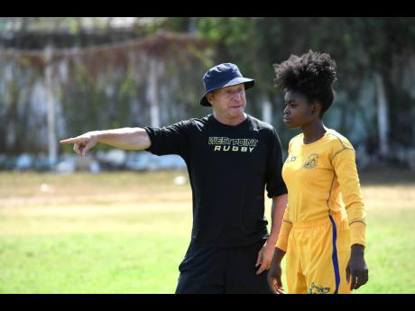 Ricardo Makyn Chief Photo Editor  Head coach Stephen Lewis (right) issues instructions to a member of the Jamaica Rugby Union Lady Crocs team during a recent training session at Emmett Park.