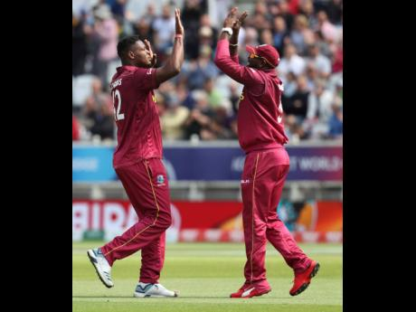 West Indies' Oshane Thomas (left) celebrates with West Indies' Ashley Nurse after bowling Australia's captain Aaron Finch, who was caught by West Indies' Shai Hope during the Cricket World Cup match between Australia and West Indies at Trent Bridge in Nottingha on Thursday, June 6, 2019. The West Indies lost the game by 15 runs.