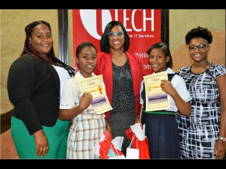 tTech Limited awarded essay winners on the heels of the PEP results. From left: Moneshe Hutchinson, human resource (HR) and training officer, tTech Limited; Sabrina Spencer, De La Vega City Homework Centre; Gillian Murray, marketing and HR manager, tTech Limited; Naricka Bryan, De La Vega City Homework Centre; and Samantha Jones, sales and marketing associate, tTech Limited.