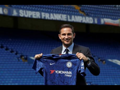 The new Chelsea manager, their former player Frank Lampard, poses for photographers with a club shirt by the pitch at Stamford Bridge stadium in London yesterday. Lampard has returned to Chelsea as the club's 12th manager in 16 years under Roman Abramovich's ownership. The former Chelsea midfielder has left second-tier club Derby, where he came close to securing promotion to the Premier League in his first season in management.