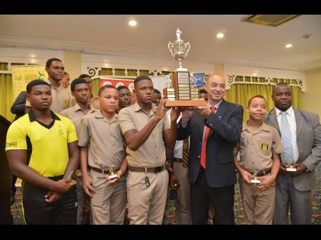 Members of Manchester High School's cricket team being presented with the ISSA/GraceKennedy Headley Cup trophy by Don Wehby, group chief executive officer of GraceKennedy Limited, during the ISSA Schoolboy Cricket Awards Ceremony, held at the Knutsford Court Hotel on Tuesday.