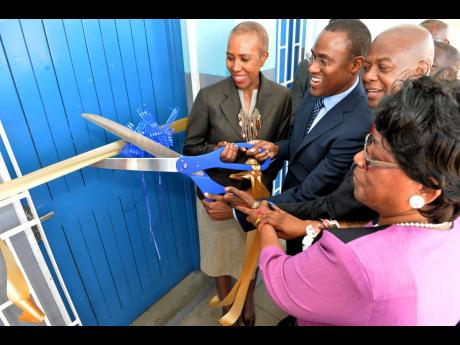 From left: Minister of Science, Energy and Technology Fayval Williams; Minister of Finance and the Public Service Dr Nigel Clarke; Chief Executive Officer of the Universal Service Fund (USF), Daniel Dawes; and principal of Maverley Primary and Junior High School Dorothy Taylor cut the ribbon to officially open a new computer lab/access point at the school earlier this year. The new lab was funded by the USF.