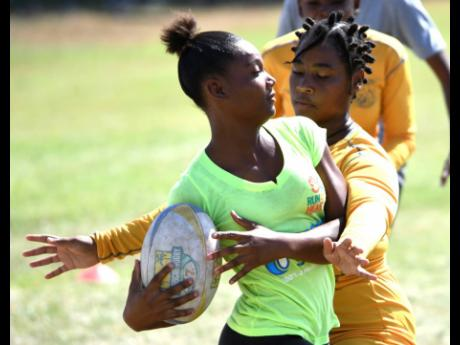 Members of the Jamaica rugby union Lady Crocs team Tihanna Lewinson (right) and Gabrielle Davidson challenge each other during a recent training session at Emmett Park.