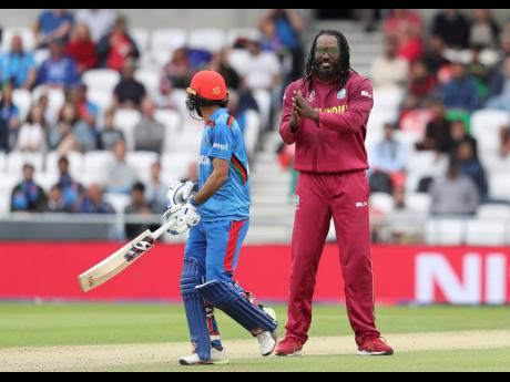 West Indies' (WI) Chris Gayle (right) celebrates the dismissal of Afghanistan's Ikram Ali during the Cricket World Cup match between Afghanistan and West Indies at Headingley in Leeds yesterday. The WI won by 23 runs.